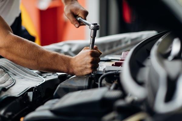 male mechanic repairs car